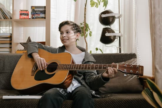 A 12 year old kid with autism playing the guitar and smiling.