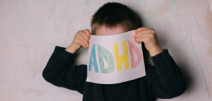 A boy holding up an ADHD sign over his face